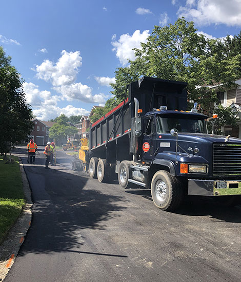 Black truck and workers paving